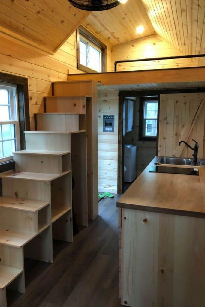 View of tiny house kitchen with blonde wood