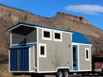 Blue and gray tiny house behind red truck
