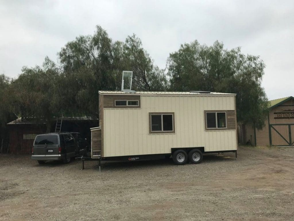 Cream colored tiny home on parking lot