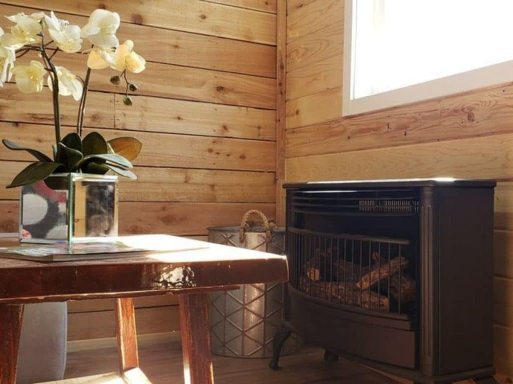 Wood stove next to silver bucket and coffee table