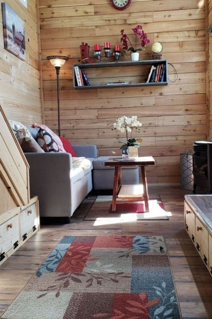 Tiny house living room with gray sofa and flip down storage in foreground
