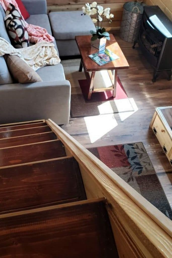 View down into tiny living room with stained wood steps