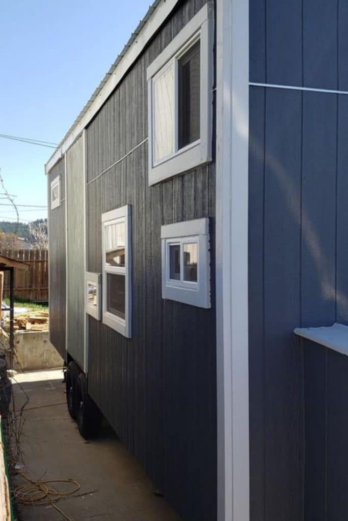 Side of blue tiny home with windows trimmed in white wood