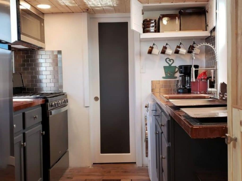 View into tiny house kitchen with gray cabinets and white walls