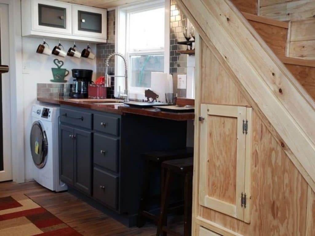 Storage under stairs leading to kitchen with laundry unit at the end of counter
