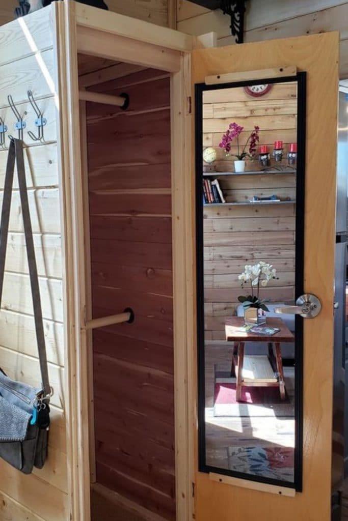 Open door to cedar closet with mirror on door