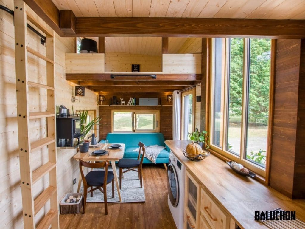 Inside of tiny home with wall of windows and light wood floors and walls