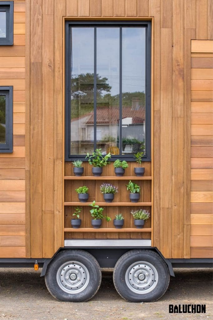 Outside of wood tiny house with shelves holding plants below large black trim window
