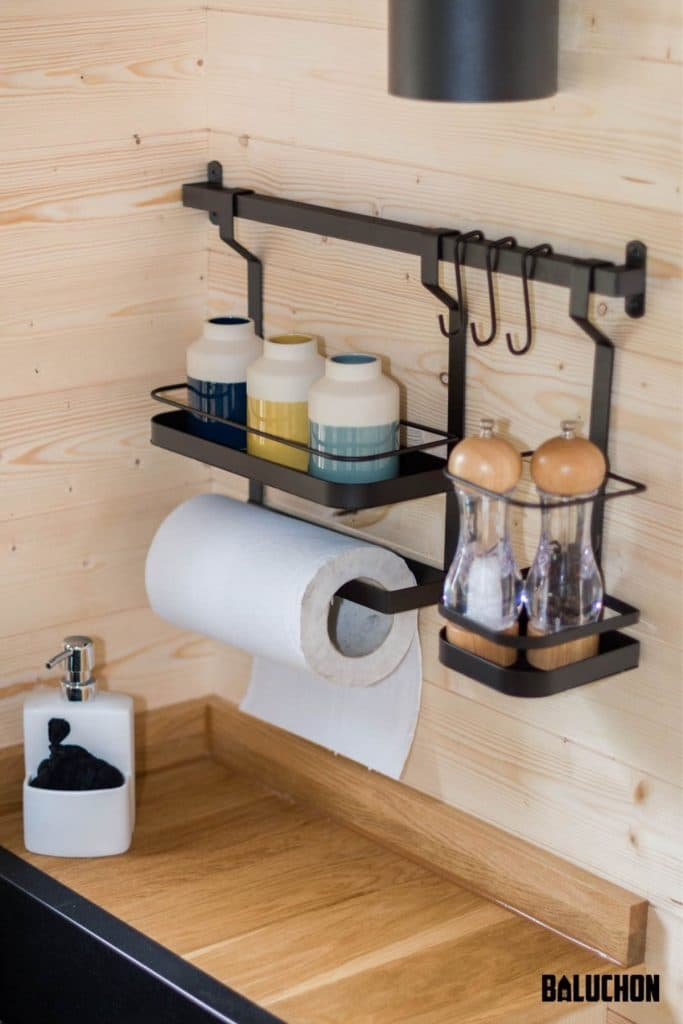 Black matte metal bar with hooks holding jars and paper towels