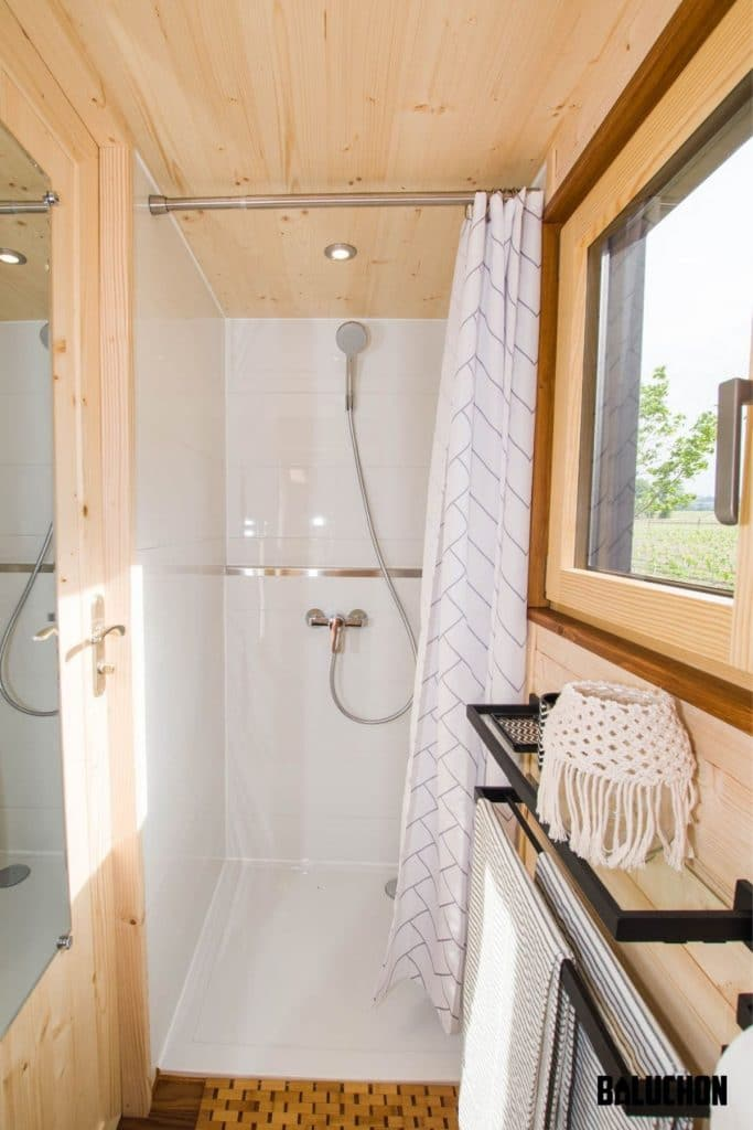 White shower stall next to large window with wood trim