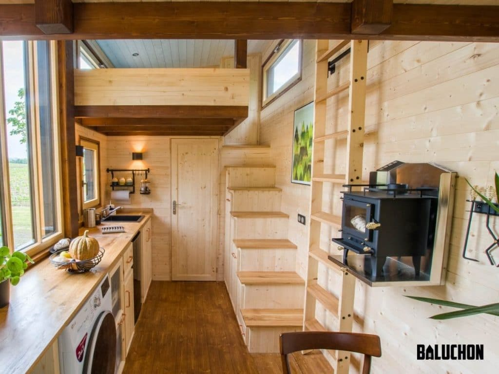 Tiny kitchen space next to wooden stairs with light wood surround walls