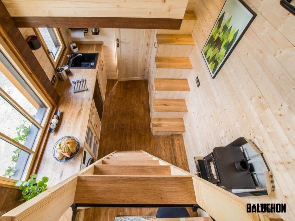 View down ladder into main floor of tiny home with light wood walls