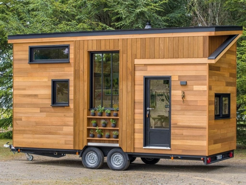 Side of tiny house on wheels with open screen door and wood siding