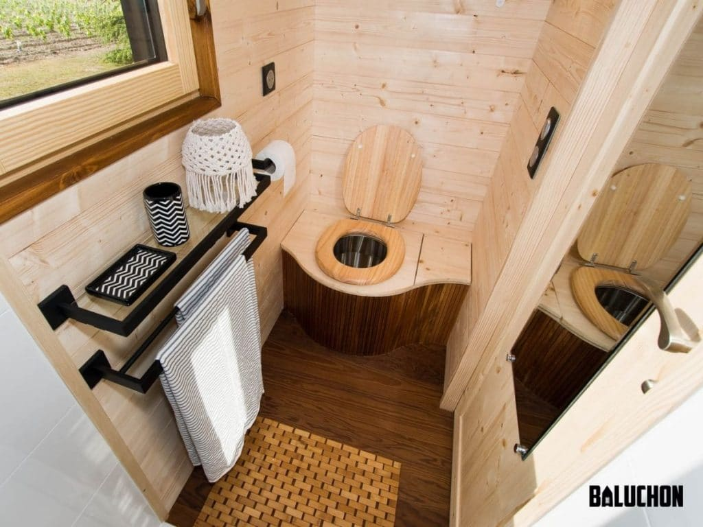 Tiny bathroom with wood toilet seat inset into wall with wood surround