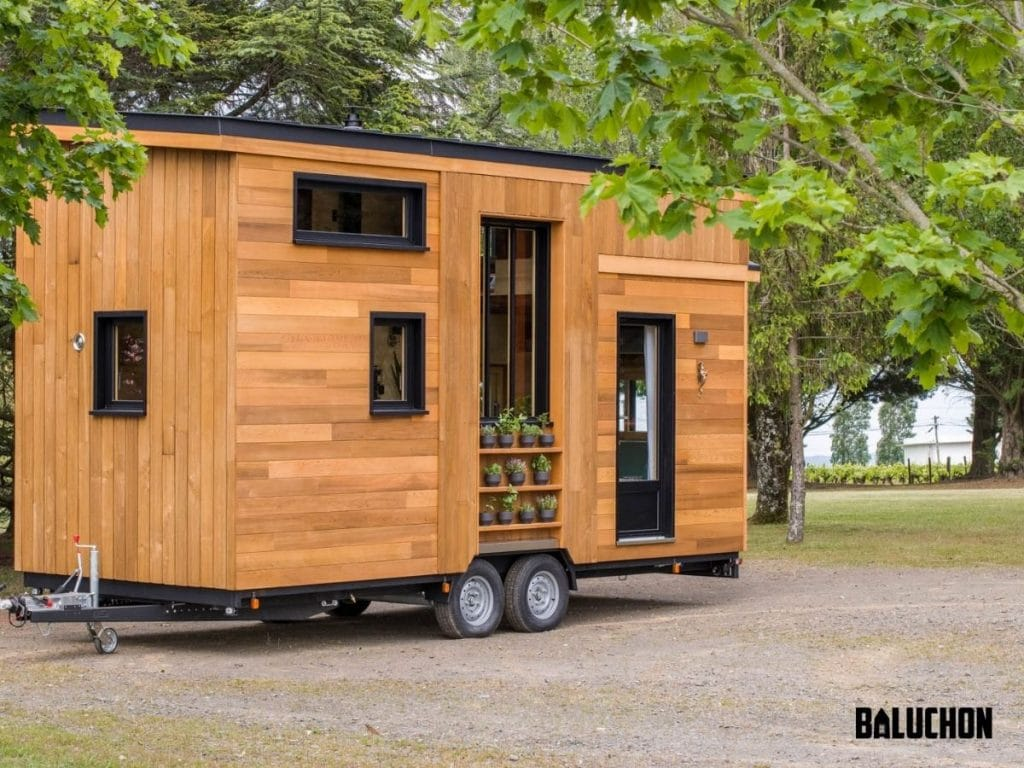 Wood tiny home with black trim on driveway net to green trees