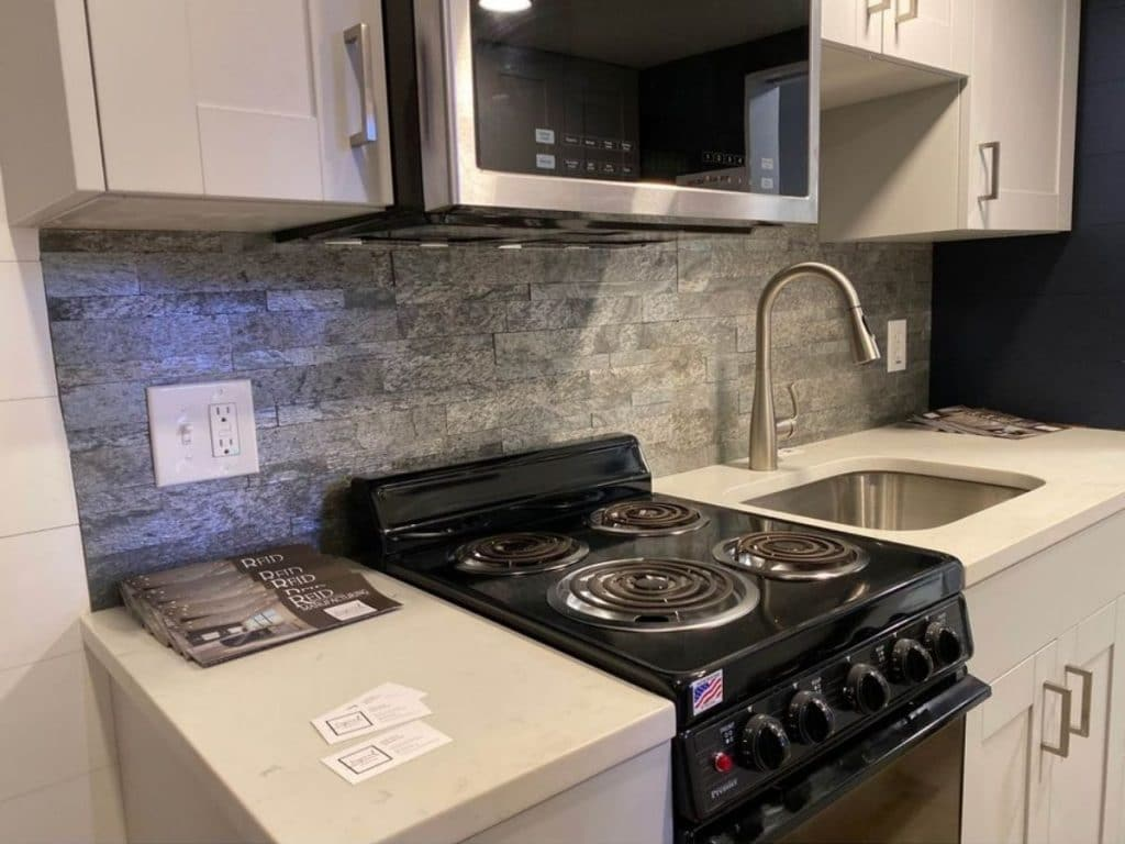 Tiny house kitchen counter with black stove next to large sink