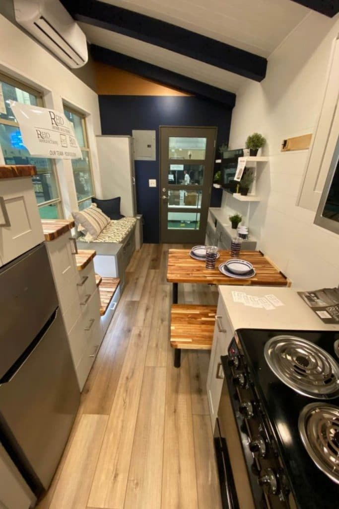 View of main tiny home space with black stove on one side and stainless steel refrigerator on opposite side