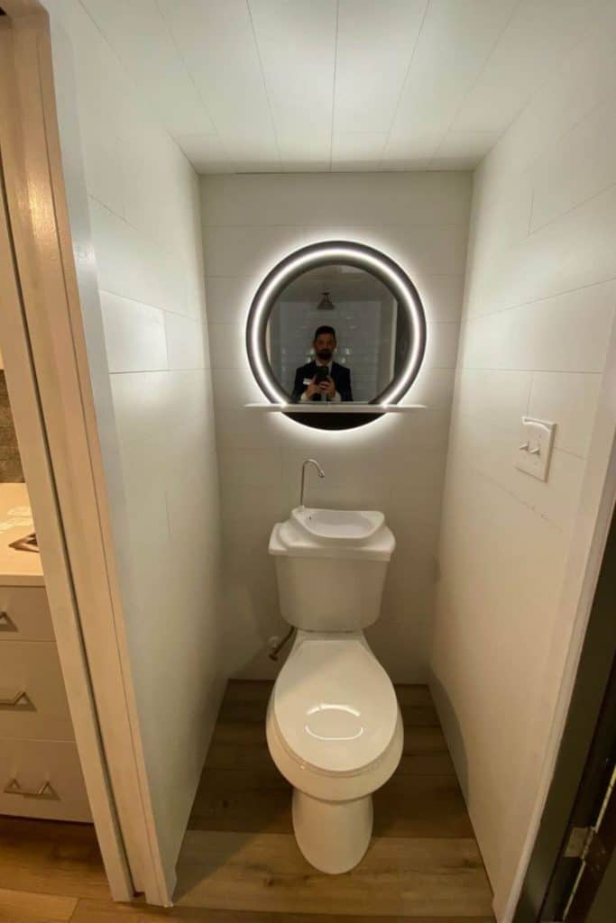 Toilet with sink in tank and round lit mirror above