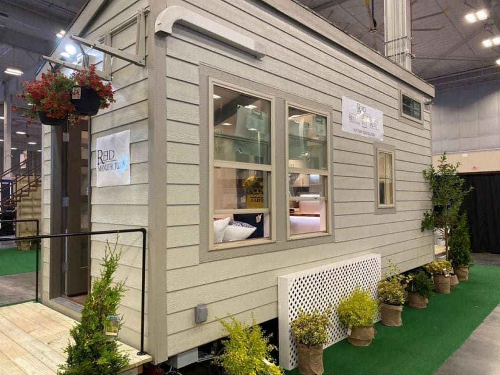 Front of tiny house with tan siding on display at show