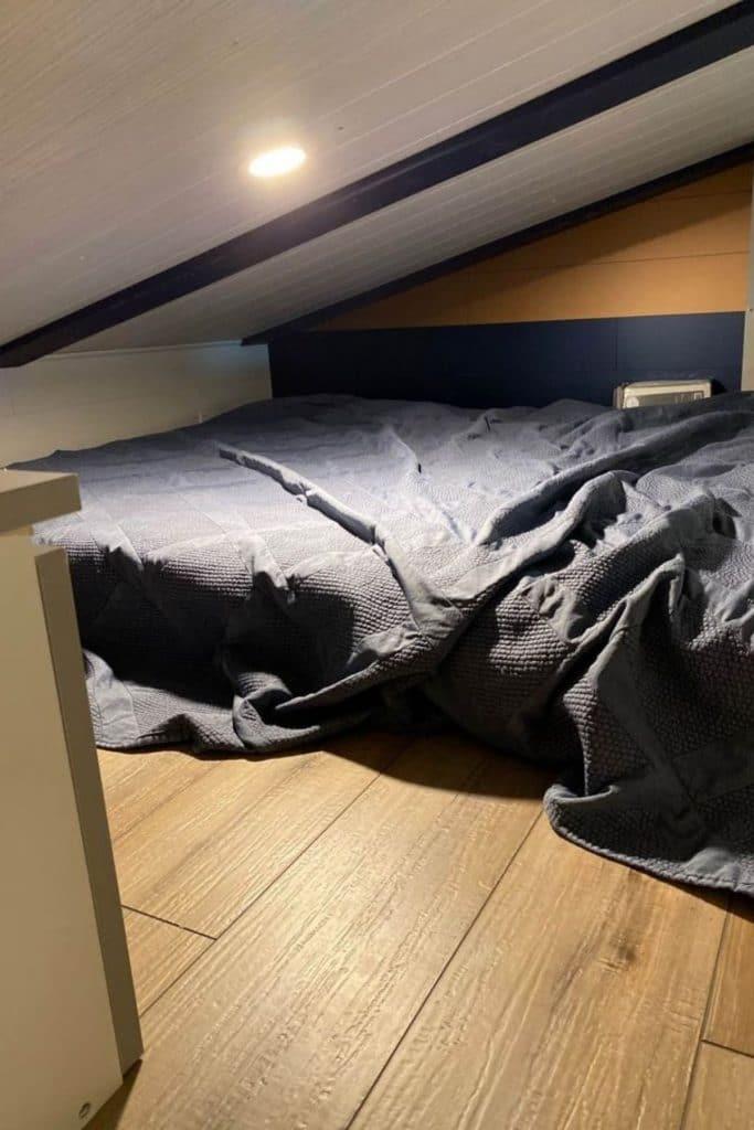Mattress in loft with dark bedding