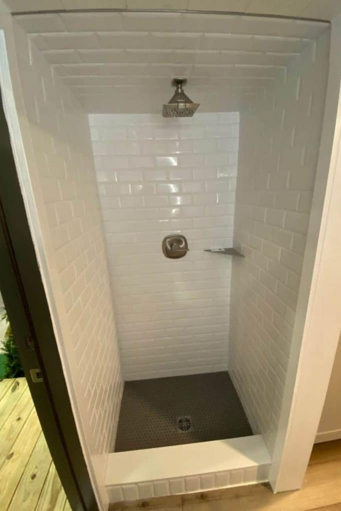 White tiled shower with faucet on back wall