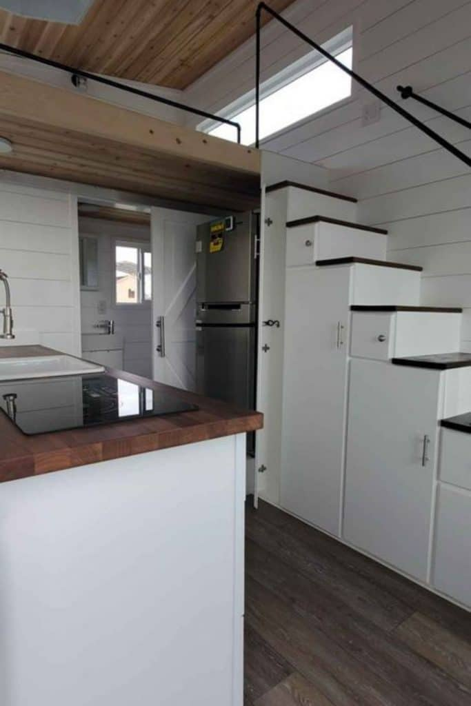 View into white kitchen with stainless steel refrigerator