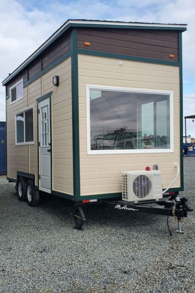 Back of tiny home on wheels with cream siding
