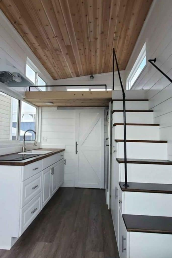 Open floor plan with kitchen below loft and stairs