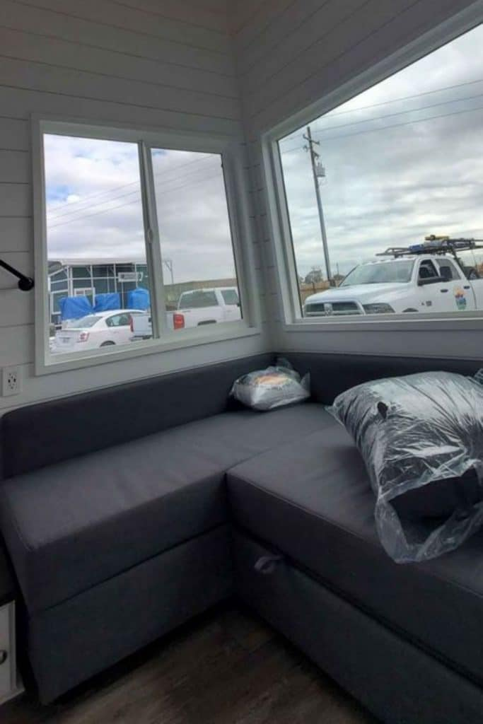 Gray bench seat under windows with underneath storage