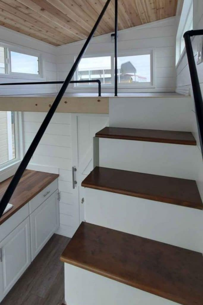 Stairs into open loft with black railing