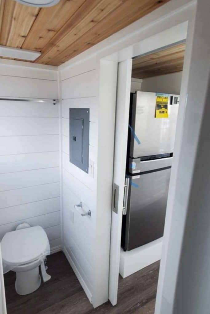 View from bathroom into kitchen showing compost toilet with wall between it and refrigerator