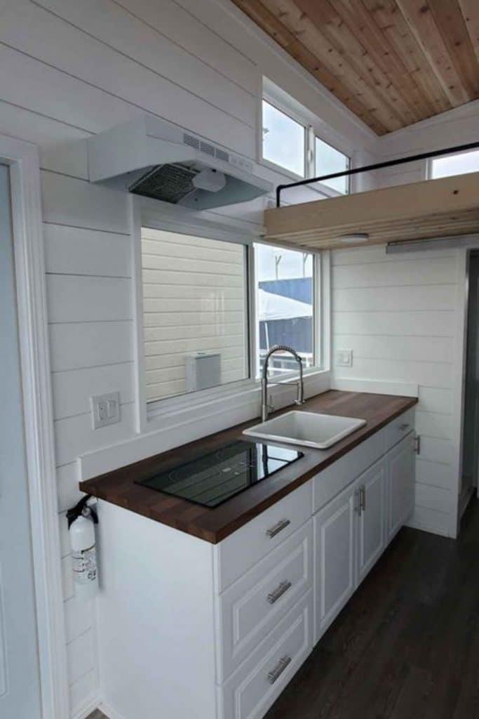 White farmhouse sink in wood kitchen counter
