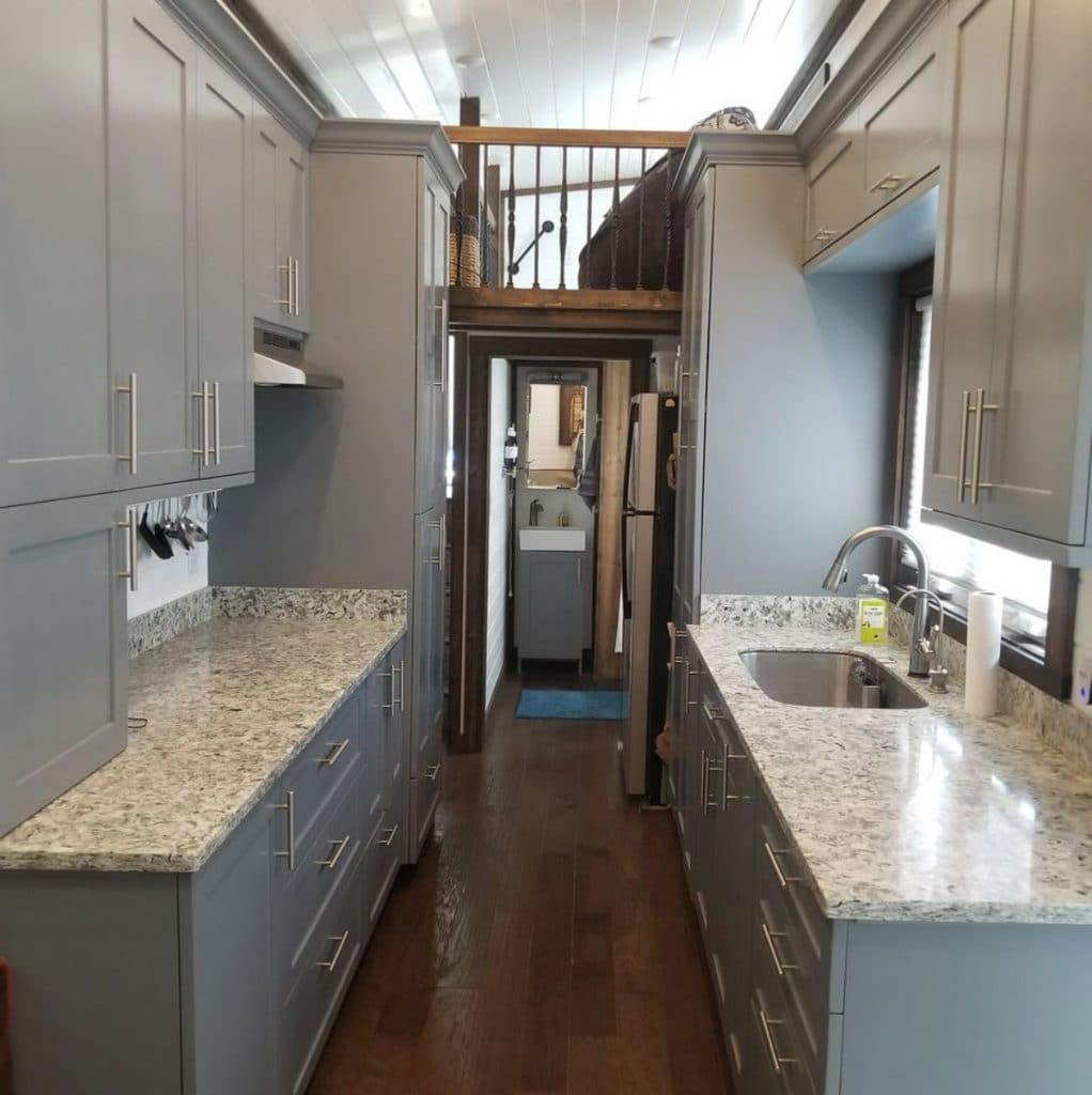 View into kitchen with granite counters and gray cabinets