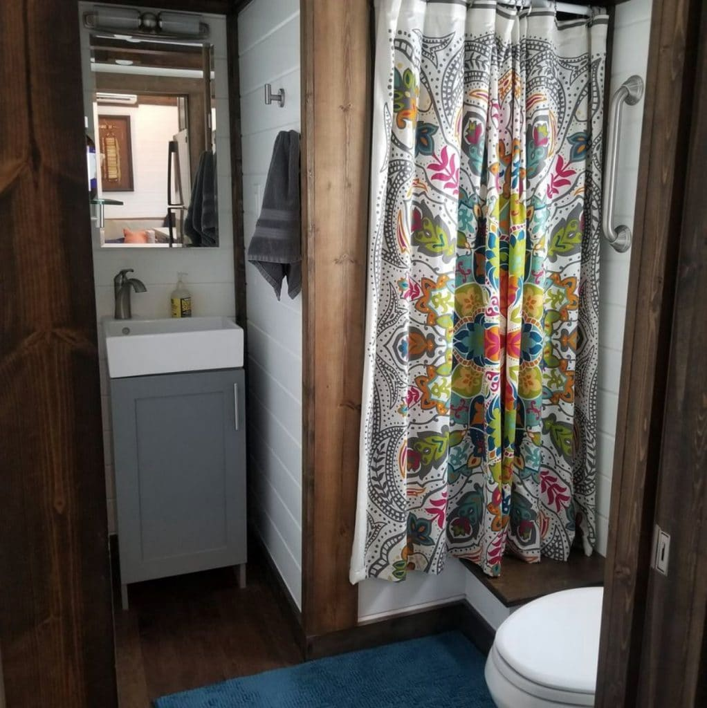Flowery curtain on shower stall with vanity to the side