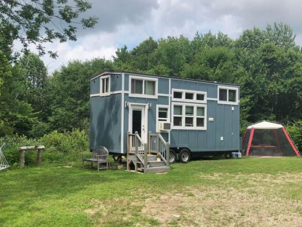 Blue tiny home in field with white trim and tent beside home
