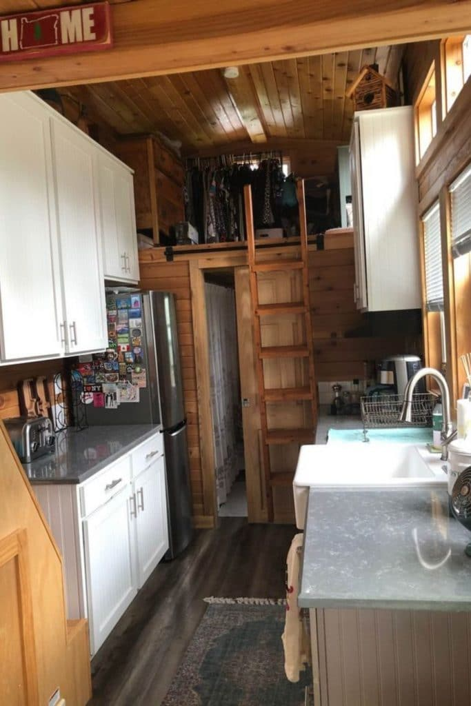 View into kitchen of tiny home showing loft at end and white cabinets