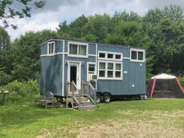 Light blue tiny house on wheels with white trim