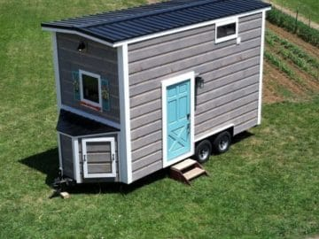 Gray tiny home with white trim on grass