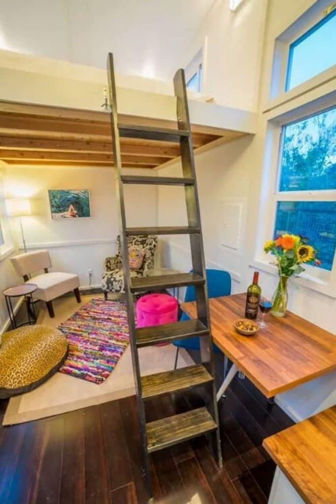 Ladder going to loft space with cozy cushions underneath in seating area