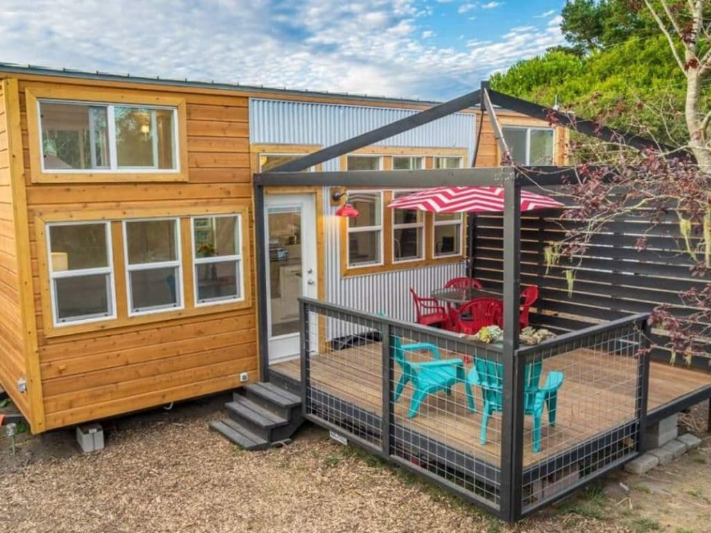 Exterior of tiny home with wood siding and large black porch with teal chairs