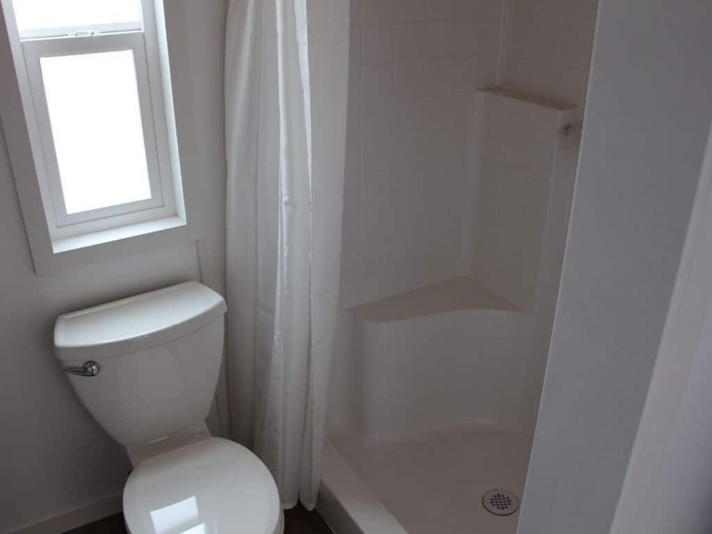 Toilet by large white shower stall