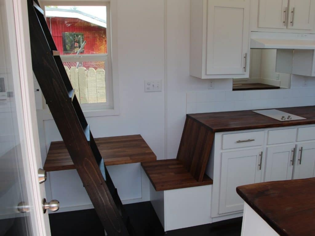 Small bench in kitchen by ladder to loft with wood top and wood table