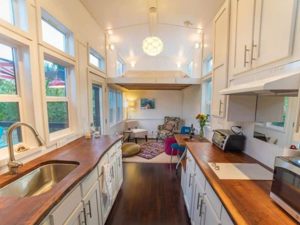 Tiny home kitchen view into living area with white cabinets and shelves