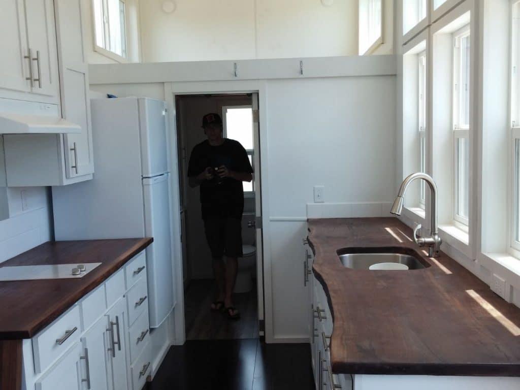 View into kitchen and bathroom doorway with man in doorway