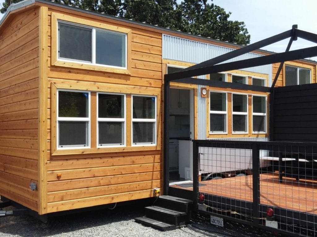 Outside of light wood and white siding tiny home with black porch attached