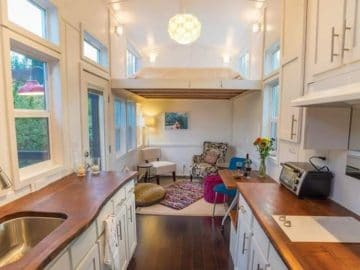 Tiny home kitchen with white cabinets and wood stained counters