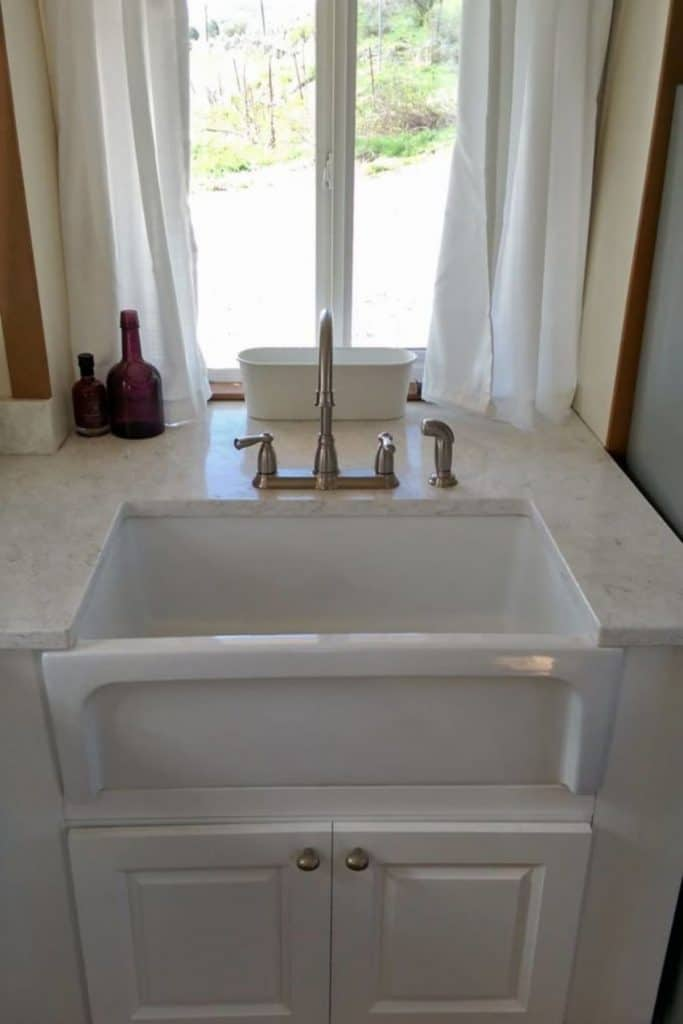 White farmhouse sink in front of window