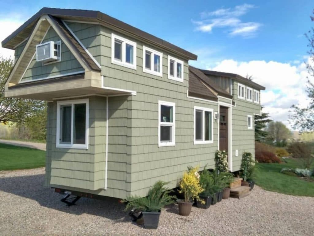 Green tiny house with two lofts parked on lot