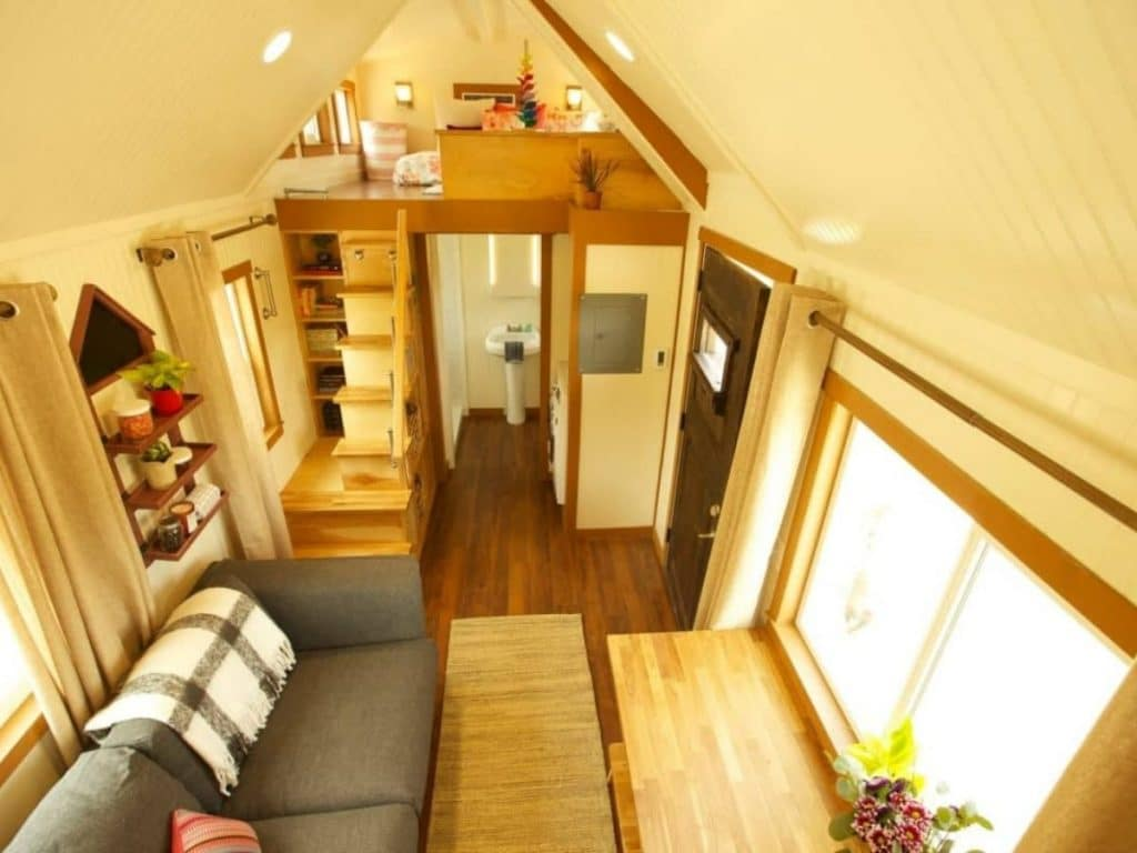 View down into tiny house living room with gray sofa