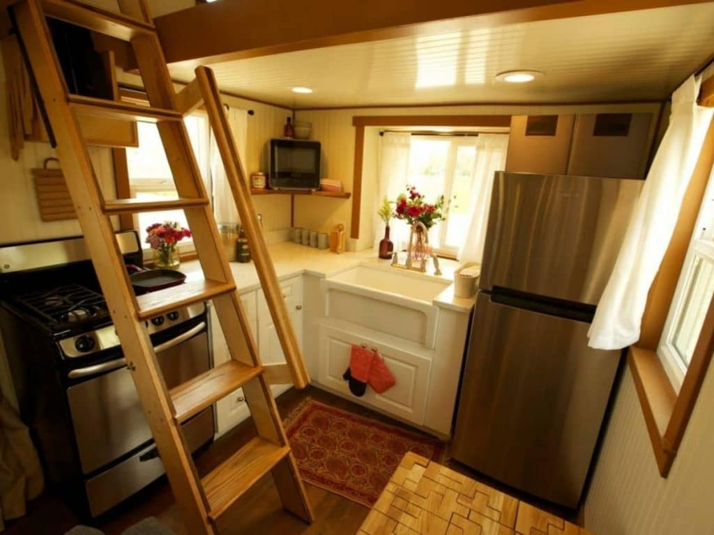 Tiny kitchen below loft with stainless steel appliances and white counters
